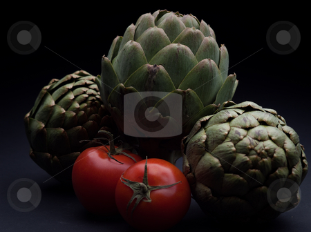 Tomatoes & Artichokes on Black stock photo, Two tomatoes nestled between three artichokes on a black background by Sharon Arnoldi