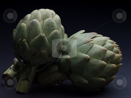 Artichoke Still Life stock photo, Three artichokes bunched together on a black background by Sharon Arnoldi