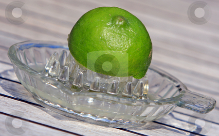 Squeezing lime juice stock photo, Half a lime in a glass juice squeezer by Karen Arnold