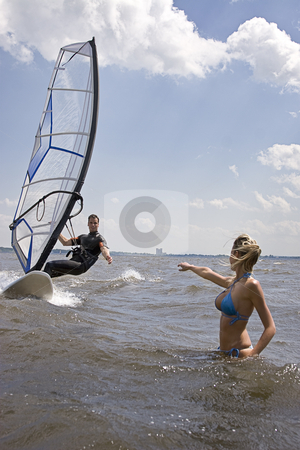 Windsurfer reaching for girlfriend stock photo, Windsurfer coming in at full speed with hand reaching for girlfriend by Yann Poirier