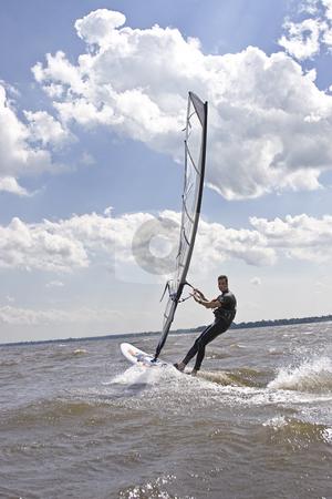 Windsurfer speeding stock photo, Windsurfer going aways at full speed by Yann Poirier