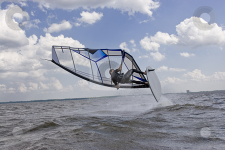 Windsurfer wipe out stock photo, Windsurfer doing a jump trick in the water and to crash by Yann Poirier
