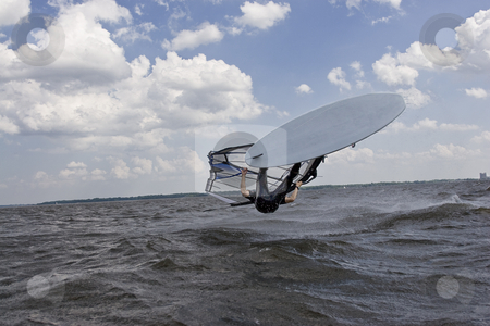 Windsurfer flipping stock photo, Windsurfer doing a flip trick in the water about to land on his back by Yann Poirier