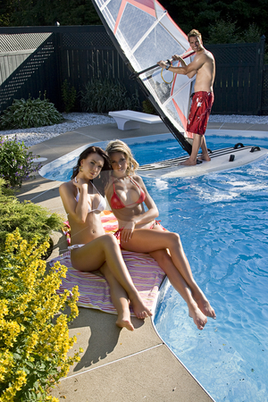 Windsurfer in pool stock photo, Windsurfer in a pool with two women tanning by Yann Poirier