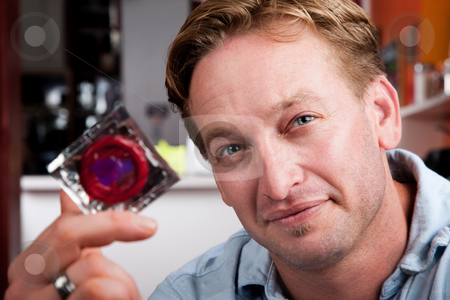 Handsome man with wrapped condom stock photo, Handsome blonde man holding a wrapped condom by Scott Griessel