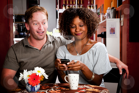 Mixed Race Couple with Handheld Phone stock photo, Mixed race Couple in Restaurant with Handheld Phone by Scott Griessel