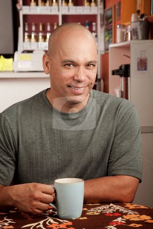 Handsome man in cafe stock photo, Handsome man with shaved head in cafe with cup by Scott Griessel