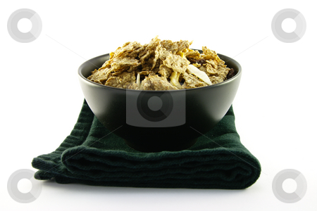 Bran Flakes in a Black Bowl stock photo, Crunchy delicious looking bran flakes in a black bowl and a black napkin on a white background by Keith Wilson