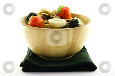 Bran Flakes in a Woodden Bowl stock photo, Crunchy delicious looking bran flakes and juicy fruit in a wooden bowl and a black napkin on a white background by Keith Wilson