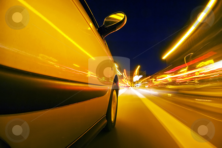 Night drive stock photo, The exterior of a car driving through an urban envrionment, with streaks of light passing by by Corepics VOF