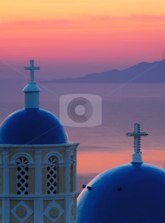 Dawn in Santorini stock photo, Image shows two church domes, typical of Santorini, against the Aegean Sea, washed in pre-sunrise colors by Andreas Karelias