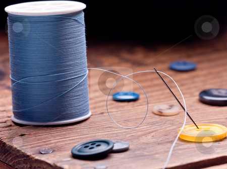 Sewing Buttons stock photo, A needle threaded with blue cotton thread rests on a yellow button by Sharon Arnoldi