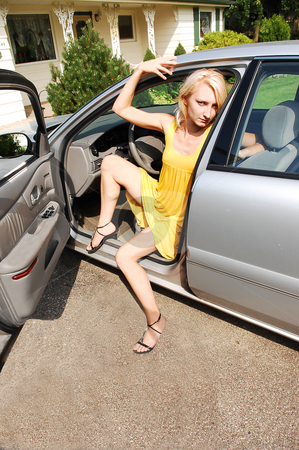 Girl sitting in the car. stock photo, A young girl in an yellow dress and long legs sitting in the car with an open door, in the driveway of her nice country house, in beautiful sunshine. by Horst Petzold