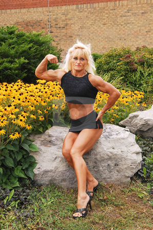 Bodybuilding woman on location. stock photo, An blond bodybuilding woman sitting on a big rock and flowers behind her, shooing her good trained and lean body. by Horst Petzold