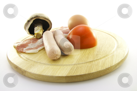Uncooked Breakfast stock photo, Uncooked sausage, bacon, mushroom, egg and tomato on a round plate with a white background by Keith Wilson