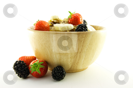 Bran Flakes in a Woodden Bowl stock photo, Crunchy delicious looking bran flakes and juicy fruit in a wooden bowl on a white background by Keith Wilson