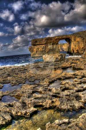 Stunning View of Azure Window in Gozo stock photo, This is a high dynamic range image of Azure Window in Gozo. It is shot at a slight angle for a more dramatic effect. Small rock formations can be sen in the foreground while the sea is visible in the distance as far as the horizon. by Stephen Kiernan