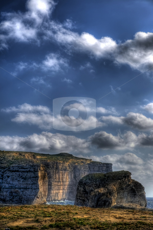 Fungus Rock on the coast of Gozo in the Mediterranean stock photo, This is a portrait image of Fungus Rock on the coast of Gozo. Clouds are high in the sky and the groung of Gozo is seen in the foreground. by Stephen Kiernan
