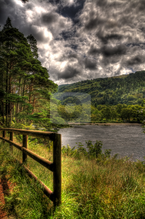 Foreboding Sky in Glendalough Ireland stock photo, A portrait view of a lake in Glendalough in Wicklow, Ireland. There is a fence in the foreground, a lake in the background and a very cloudy sky. by Stephen Kiernan