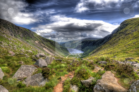 Wide angle view of Glendalough stock photo, A wive angle view of Glendalough in Co. Wicklow Ireland. Hills can be seen on both sides of the image and there is a lake in the far backgound in the distance. There are rocks and grass in the foreground. by Stephen Kiernan