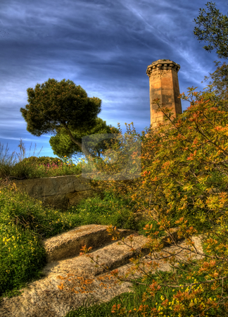Malta Watchtower Rising from the Bush stock photo, This is a portrait view of a trees beside a watchtower in Valetta, Malta. There are yellow leaves on the branches and stone steps beside the bushes. by Stephen Kiernan