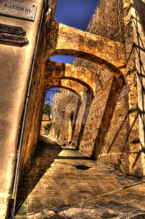 Stone Archways in Mdina stock photo, This is a portrait view of an archway in Mdina, Malta. There are shadows cast from the surrounding objects. Three stone arches lead into the background along the pathway. by Stephen Kiernan