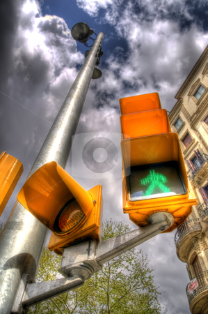 Traffic Lights In Barcelona stock photo, This is a portrait shot of a set of traffic lights in Barlecona near La Rambla. The traffic pole is seen to extend into the clouds due to the unusal perspective and manner in which the image is composed. by Stephen Kiernan
