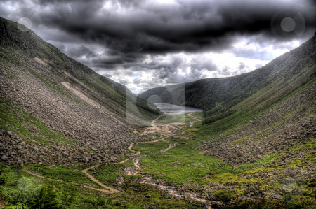 Glendalough Under An Angry Sky stock photo, A scene of Glendalough, Co Wicklow, Ireland on a dark day. The are clouds of many colours and the view is foreboding. The valley can be seen and there is a lake in the middle. by Stephen Kiernan