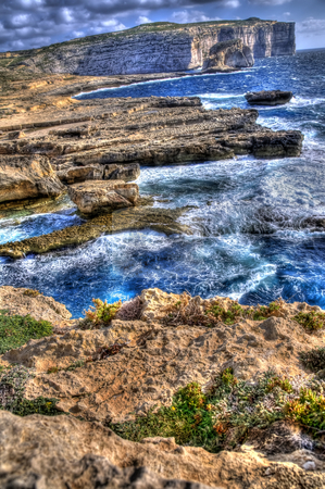 Waves Crashing on The Shore of Gozo stock photo, An off angle image of the shores of Gozo. Fungus Rock can be clearly seen in the background. by Stephen Kiernan