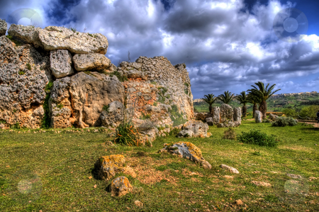 Ggantija Temple Remains in Gozo stock photo, An image of the 7000 year old ancient ruins of Ggantija in Gozo. Palm trees can be seen in the background and there are many clouds in the sky. by Stephen Kiernan