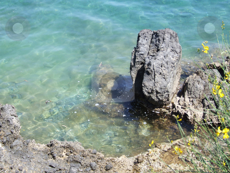 Rock in clear water stock photo, A rock sitting in clear blue water on the coast of Corfu. by Stephen Kiernan
