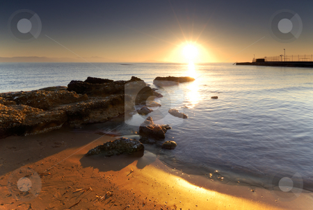 Mediterranean sunrise stock photo, A very bright sunrise over a Mediterranean rocky seascape. by Andreas Karelias