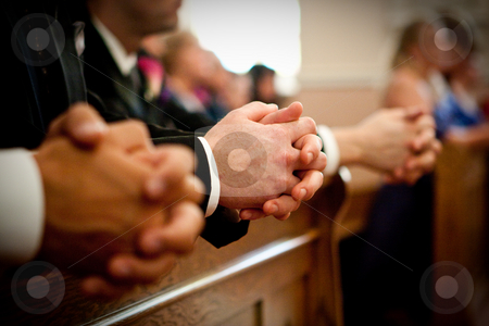 Clasped hands during a prayer stock photo, During a wedding ceremony guests kneel down during a prayer by Sharon Arnoldi