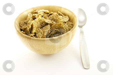 Bran Flakes in a Woodden Bowl stock photo, Crunchy delicious looking bran flakes in a wooden bowl with a spoon on a white background by Keith Wilson