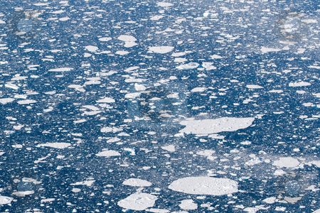 Ice sheets in the ocean stock photo, White sheets of ice in the deep blue ocean water by Anders Peter