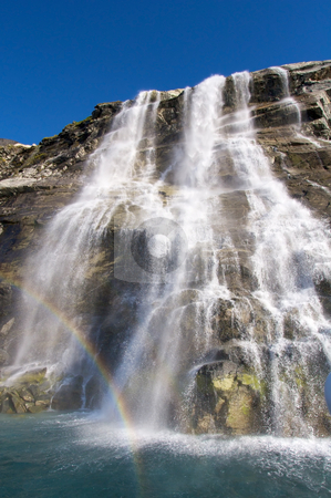 Waterfall and rainbow stock photo, Huge waterfall at the backside of moutain Sermitsiaq. There is a rainbow in front of the water. by Anders Peter