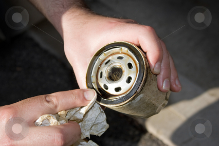Dirty Used Oil Filter stock photo, A backyard mechanic wipes the seal of  a slightly used oil filter to reuse it for an additional 3000 miles.  Others prefer to replace them each and every oil change. by Todd Arena
