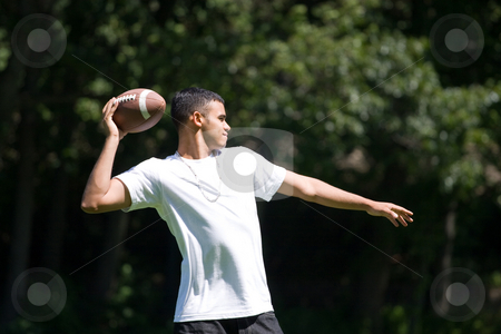 Man Throwing a Football stock photo, A young man throwing a football outdoors. by Todd Arena