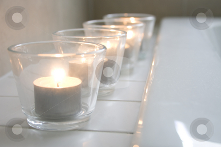 Tealight candles in a row stock photo, Row of tealight candles on the edge of a bathtub by Jodie Johnson
