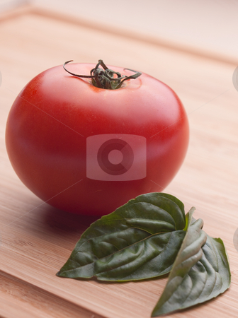 Handpicked tomato with Basil stock photo, One red tomato on a cutting board with Basil by Sharon Arnoldi