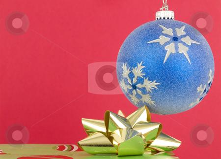 Christmas ornament and present stock photo, Christmas ornament and present on a red background by John Teeter