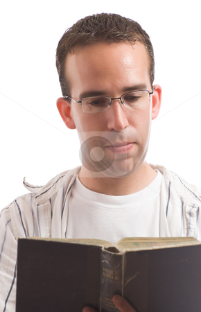 Man Reading A Bible stock photo, A young man wearing glasses is reading an old bible, isolated against a white background by Richard Nelson