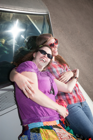 Women resting on a car hood stock photo, Women resting on the hood of an old car by Scott Griessel