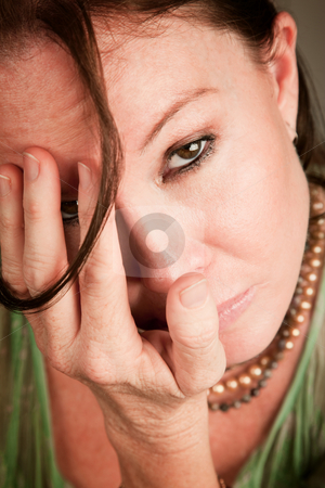 Sad woman covering her face stock photo, Sad woman covering her face with a hand by Scott Griessel