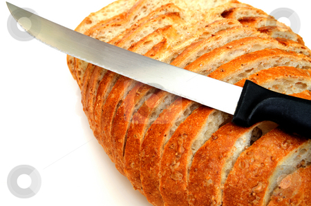 Cracked Wheat Sourdough Bread stock photo, Sliced fresh sourdough bread with a serrated knife on a white background. by Lynn Bendickson