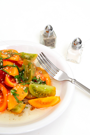 Tomato Salad stock photo, Different types of heirloom tomatoe wedges with thinly sliced basil leaves, sesame seeds and an olive oil and raspberry vinegar dressing by Lynn Bendickson