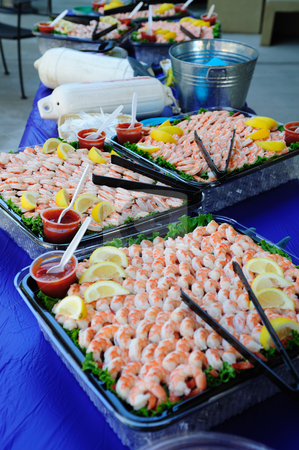 Shrimp And Lemon Wedges stock photo, Large trays of shelled and cooked shrimp with lemon slices and seafood sauce. by Lynn Bendickson