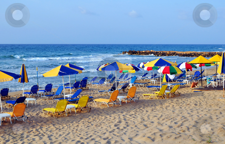 Sunbeds and beach umbrellas stock photo, Travel photography: summer: sunbeds and umbrellas in mediterranean beach. by Fernando Barozza
