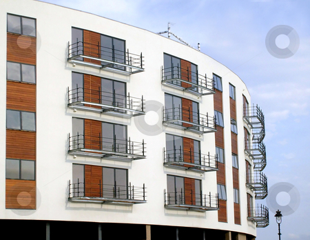 Modern apartment building stock photo, Architectural details of modern apartment building with blue sky background. by Martin Crowdy