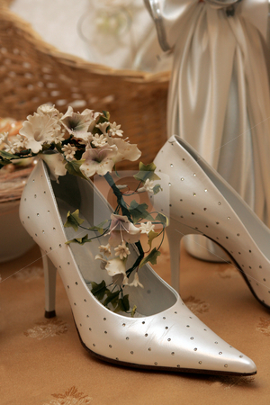 Bridal wedding shoes stock photo, Pair of bridal wedding shoes decorated with flowers, satin dress in background. by Martin Crowdy